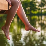 woman sitting on dock over water dangling legs