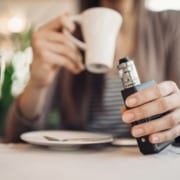 Young woman using vape to smoke in public places